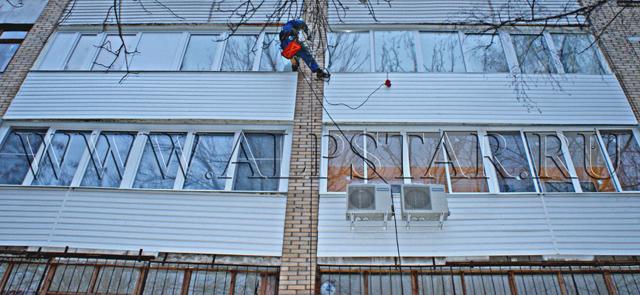 Фото. Промышленные альпинисты выполняют работы по обшивке сайдингом двух лоджий