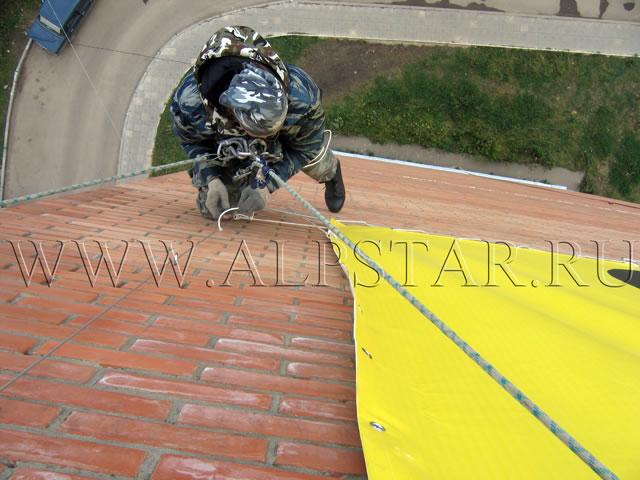 Фото. Промышленные альпинисты шнуруют банер
