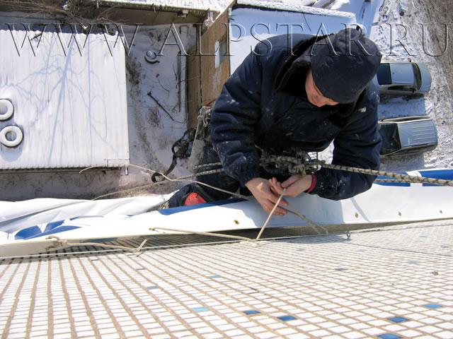 Фото. Промышленные альпинисты пришнуровывают банер на раму
