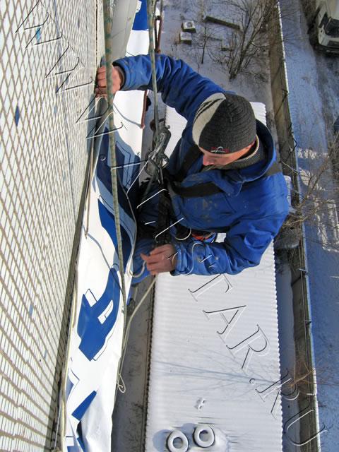 Фото. Промышленный альпинист шнурует банер на раму