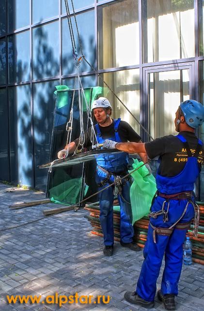 Промышленные альпинисты принимают стеклопакет